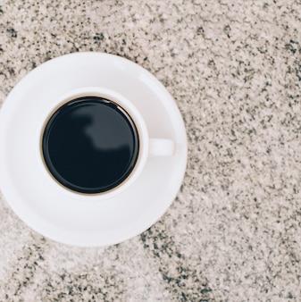 Een bovenaanzicht van een koffiekopje en een schotel op marmeren gestructureerde achtergrond