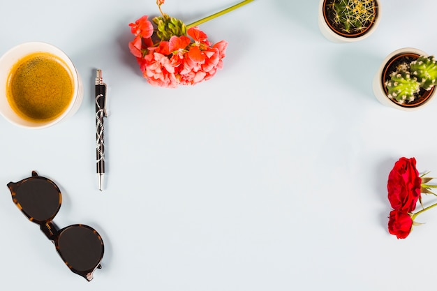 Een bovenaanzicht van een kopje thee; pen; zonnebril; cactus plant en rozen op witte achtergrond