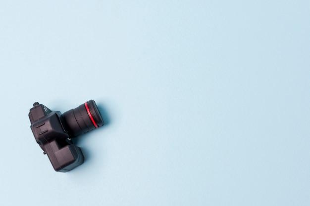 Een bovenaanzicht van een kunstmatige zwarte camera op blauwe achtergrond