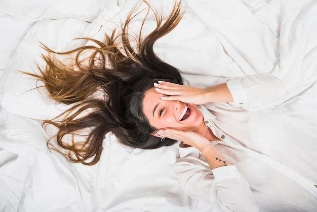 Een bovenaanzicht van een lachende jonge vrouw die hij oog met hand liggend op bed