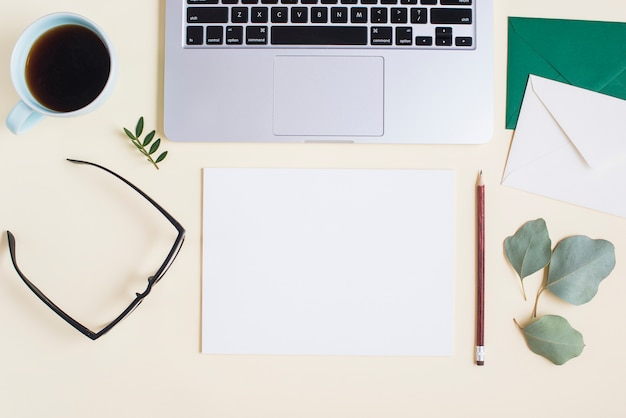 Een bovenaanzicht van een laptop met briefpapier en kopje thee op gekleurde achtergrond