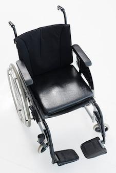 Een bovenaanzicht van een lege rolstoel tegen een witte achtergrond