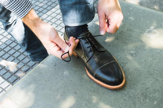 Een bovenaanzicht van een man die zijn schoenveter bindt