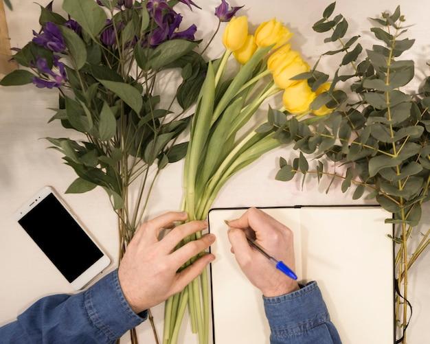 Een bovenaanzicht van een mannelijke bloemist schrijven op dagboek met pen op tafel met bloemen