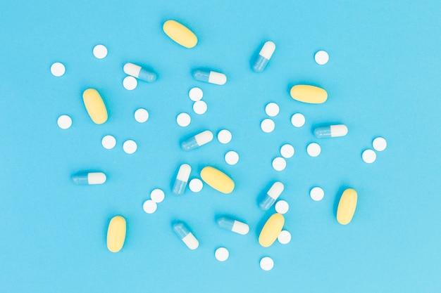 Een bovenaanzicht van een medische pillen op blauwe achtergrond