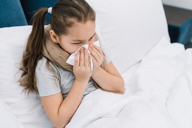 Een bovenaanzicht van een meisje dat lijdt aan verkoudheid en hoest