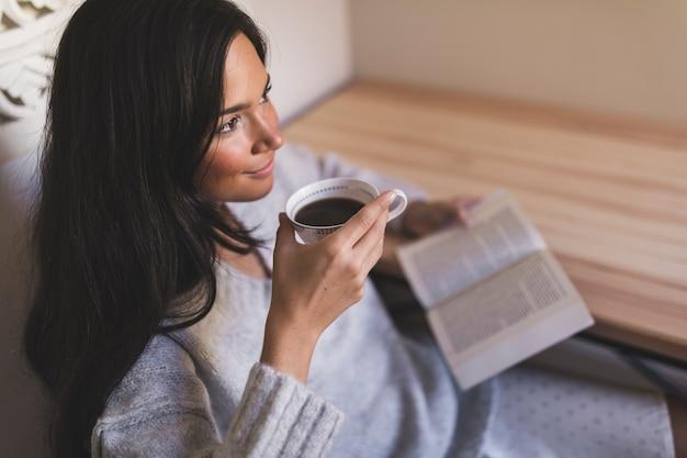 Een bovenaanzicht van een meisje met boek drinken koffie