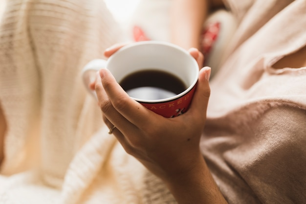 Een bovenaanzicht van een meisje met koffiekopje in handen