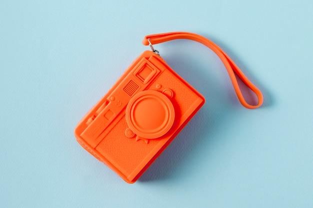 Een bovenaanzicht van een oranje tas in camera vorm op blauwe achtergrond