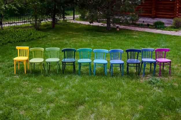 Een bovenaanzicht van een rij kleurrijke weense stoelen op een rij een hobby voor het schilderen van oude meubels en een ...