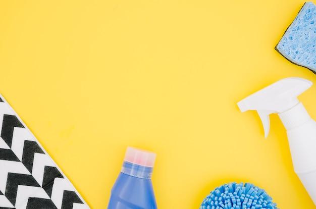 Een bovenaanzicht van een spray fles en spons op gele achtergrond