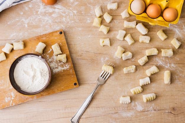 Een bovenaanzicht van een vork voor het voorbereiden van de verse italiaanse pasta gnocchi op houten bureau