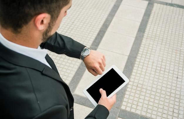 Een bovenaanzicht van een zakenman op zoek naar zijn horloge mobiele telefoon in de hand te houden