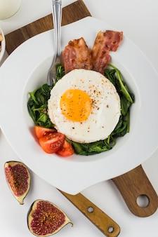 Een bovenaanzicht van ei met spek; fig; spinazie en tomaat op witte plaat tegen een witte achtergrond