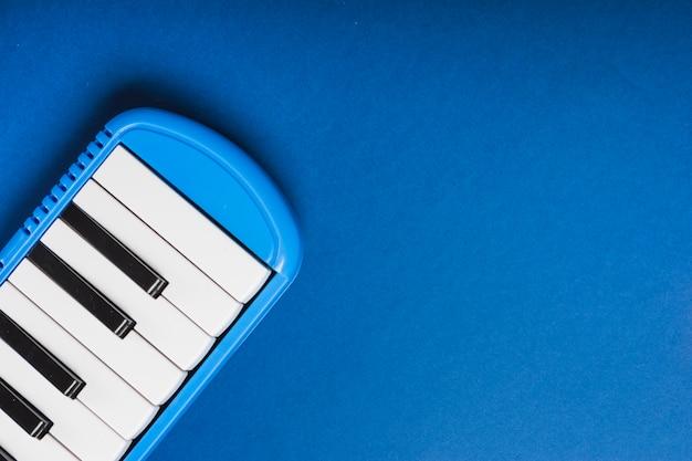 Een bovenaanzicht van elektronische synthesizer op blauwe achtergrond