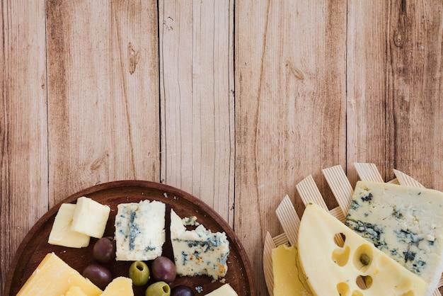 Een bovenaanzicht van emmental; gouda en blauwe kaas op coaster en snijplank