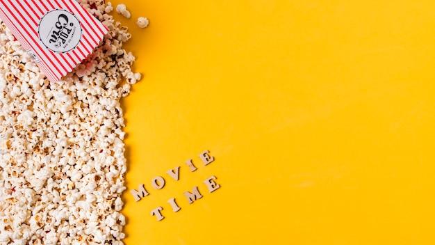 Een bovenaanzicht van filmtijd tekst in de buurt van de popcorns tegen gele achtergrond