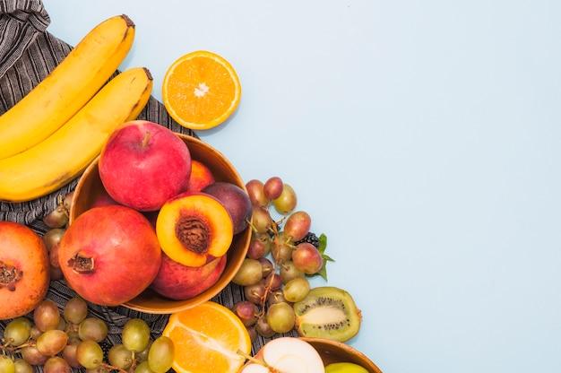 Een bovenaanzicht van fruit; banaan; druiven; kiwi en perzik op blauwe achtergrond