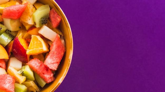 Een bovenaanzicht van fruitsalade in kom tegen paarse achtergrond