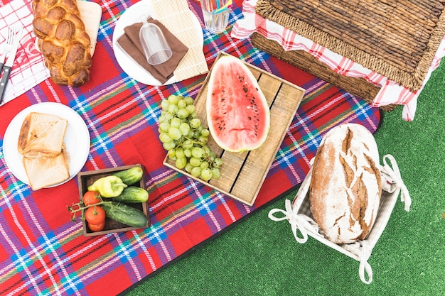 Een bovenaanzicht van gebakken brood; fruit en picknickmand op deken