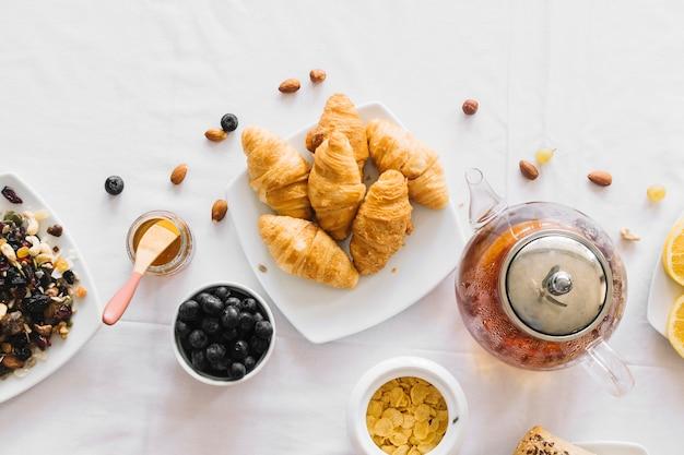 Een bovenaanzicht van gebakken croissant; vruchten; thee en dryfruits op wit tafelkleed