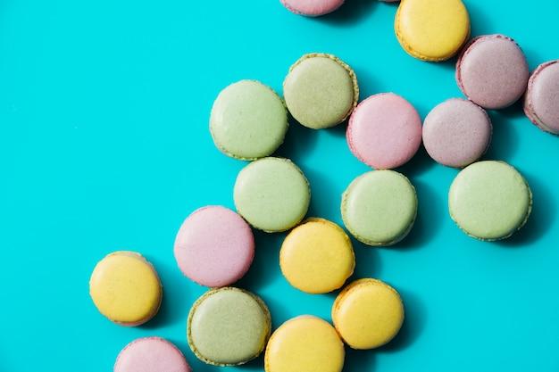 Een bovenaanzicht van gebakken groen; gele en roze bitterkoekjes op blauwe achtergrond