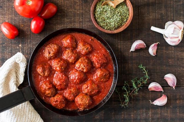 Een bovenaanzicht van gehaktballen in zoetzure tomatensaus met ingrediënten