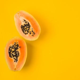 Een bovenaanzicht van gehalveerde papaja met zaden op gele achtergrond