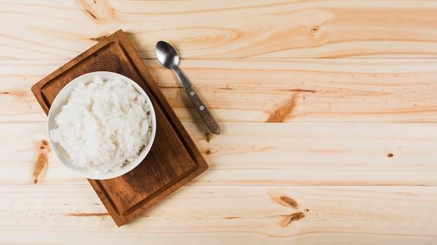 Een bovenaanzicht van gekookte witte rijst kom op houten dienblad met lepel