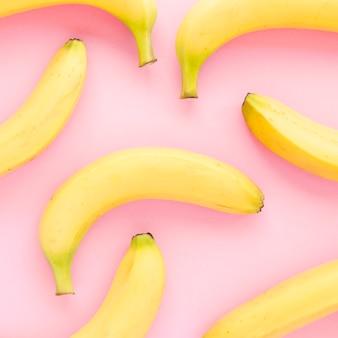 Een bovenaanzicht van gele biologische bananen op roze achtergrond