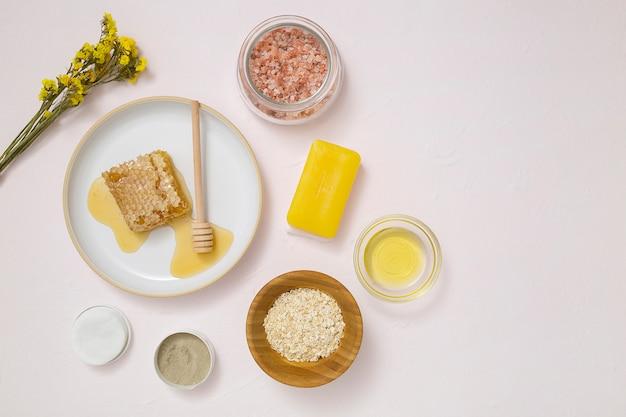 Een bovenaanzicht van gele bloem; wattenschijfjes; haver; essentiële olie; zeep en himalayan-rotszout op witte geweven achtergrond