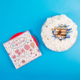Een bovenaanzicht van gelukkige verjaardagskaart op plaat met verjaardagstaart tegen blauwe achtergrond