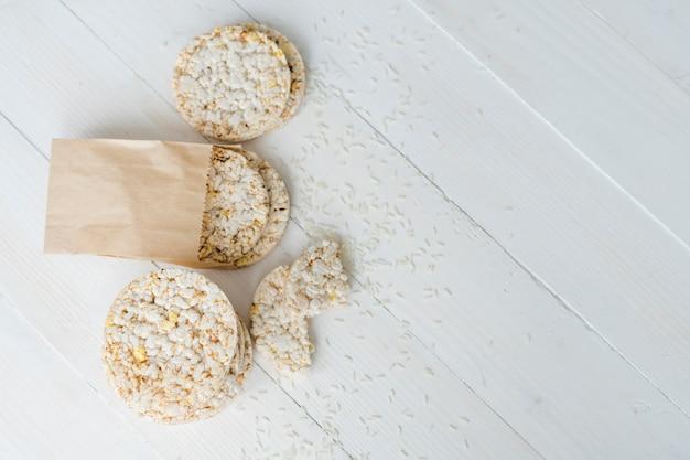 Een bovenaanzicht van gepofte rijst met granen op witte houten bureau