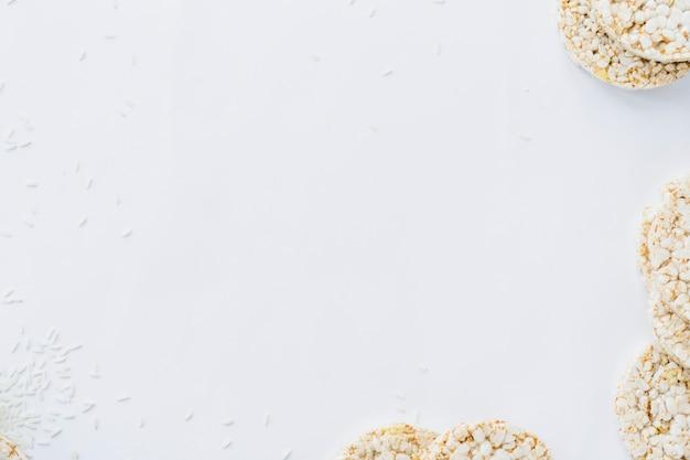 Een bovenaanzicht van gepofte rijstwafels met granen op wit papier