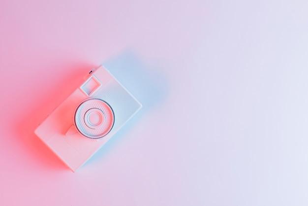 Een bovenaanzicht van geschilderde camera tegen roze achtergrond