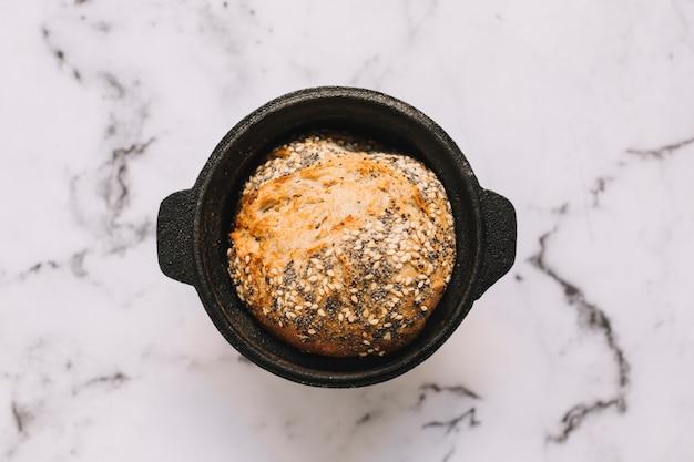 Een bovenaanzicht van gezond brood met zaden in de container op marmeren blad