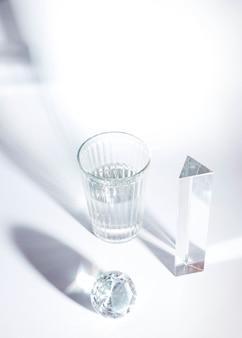 Een bovenaanzicht van glanzende diamant; prisma en glas met schaduw op witte achtergrond