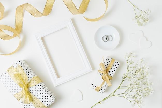 Een bovenaanzicht van gouden lint met geschenkdozen; gestel; trouwringen en baby's-adem bloemen op witte achtergrond