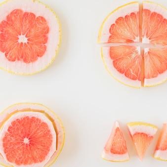 Een bovenaanzicht van grapefruit gesneden in verschillende vorm en plak over de witte achtergrond