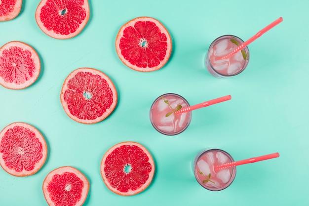 Een bovenaanzicht van grapefruits plakjes en glas sap met ijs en mint op pastel achtergrond
