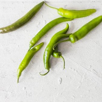 Een bovenaanzicht van groene pepers op witte textuur achtergrond