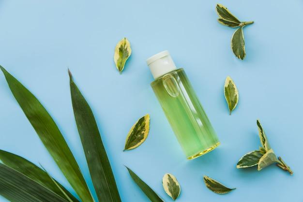 Een bovenaanzicht van groene spray fles met groene bladeren op blauwe achtergrond