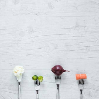 Een bovenaanzicht van groenten op vork gerangschikt op houten tafel