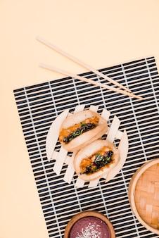 Een bovenaanzicht van gua bao vlees en kip aziatisch eten op placemat met stokjes tegen beige achtergrond
