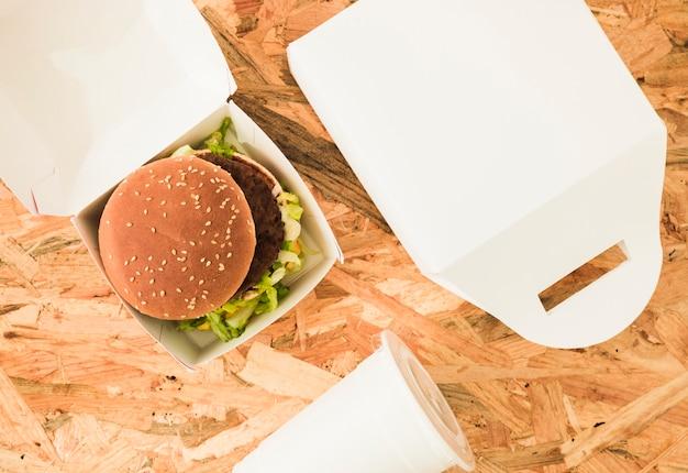 Een bovenaanzicht van hamburger in pakket over de houten achtergrond
