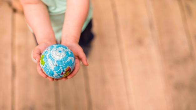 Een bovenaanzicht van handen met globe bal tegen hardhouten vloer