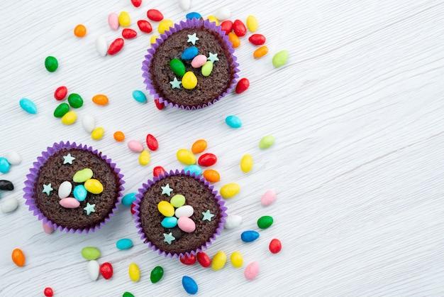 Een bovenaanzicht van heerlijke brownies in paarse vormen met kleurrijke snoepjes op wit, snoepkleurige snoepjes