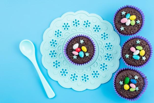 Een bovenaanzicht van heerlijke brownies in paarse vormen, samen met kleurrijke snoepjes op blauwe, snoepkleurige snoepjes