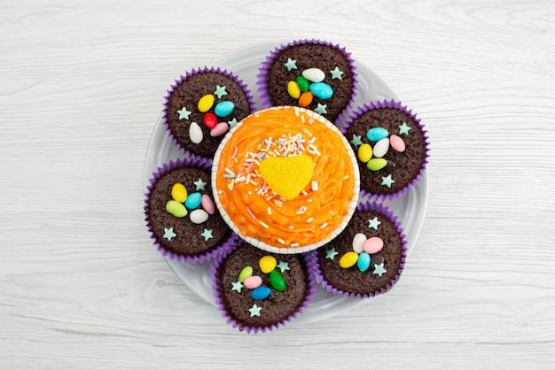 Een bovenaanzicht van heerlijke brownies in paarse vormen, samen met kleurrijke snoepjes op witte, snoepkleurige snoepjes
