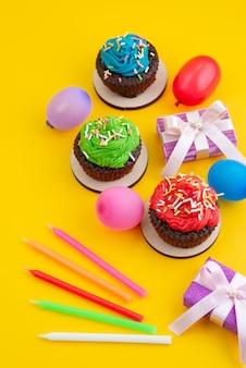 Een bovenaanzicht van heerlijke brownies op basis van chocolade, samen met snoepjes en ballen op gele, snoepcake koekjeskleur